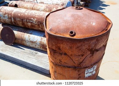 A severely damaged 55-gallon steel drum. Steel drum is rusty, scratched, dented and bulging.