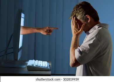 Severely distraught man sitting in front of a computer with a judgmental hand pointing at him from within the computer monitor showing being computer bullying bullied or stalked on social media.