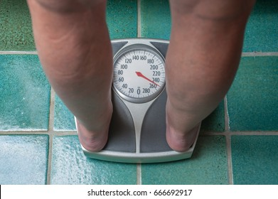A severely overweight person weighing herself or himself on a bathroom scale