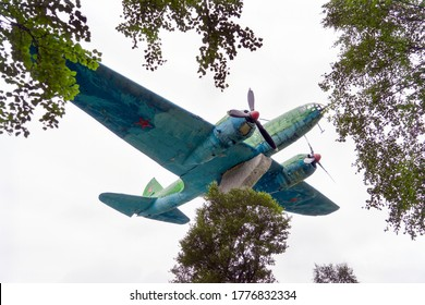 Severomorsk, Russia - August, 2019: Commemorative sign in honor of Severomorsk aviators served in the World Second War.. Torpedo Bomber IL-4 on stone pedestal on white sky background.