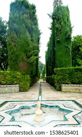 Sevilla, Andalusia / Spain - November 4, 2018:  passageway in the middle of the royal gardens, Real Alcazar, UNESCO Humanity Heritage.