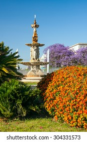Sevilla beutiful colorful garden with statue and trees in blossom in spring