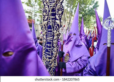 Sevilla, Spain - April 18th 2014: Holy week easter procession of cucuruchos wearing violet costumes in cone shape hats