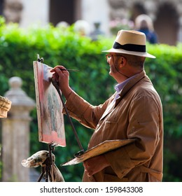 Sevilla, Spain: April 27, 2013 - A street artist painting a picture of famous motive with oil colors. Old traditional European cities are widely used by street artists to practice Arts.
