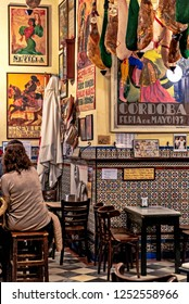 Sevilla, Spain. Circa March 2016. Typical patio restaurant in Seville, Spain, with serrano hams hanging from the ceiling and colorful pictures and tiles decorating the walls.