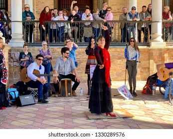 Sevilla, Spain - february 26, 2019. Female flamenco dancer in traditional dress, young woman dancing flamenco, street band and flamenco dancer on the square of Spain, Sevilla.