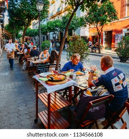 Sevilla, Spain - July 15, 2018: Tourists enjoy at restaurant terrace typically Spanish cuisine, seafood paella with squids, mussels, clams, and prawns on a bed a saffron flavoured rice