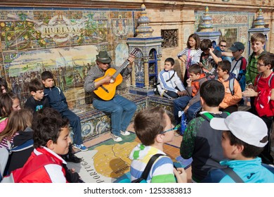 Seville, Andalusia, Spain - April 12, 2012: Guitarist busker plays for the group of school children on Plaza de Espana, bench and wall decorated with Azulejos tiles.
