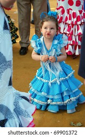 SEVILLE - APRIL 28: Even the youngest girls dress traditional flamenco dresses during the Feria de Abril on April 28, 2009 in Seville, Spain. Unidentified little girl