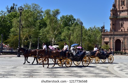 SEVILLE - SPAIN / 04.05.2017: Plaza de Espana Seville, view of tourists riding in carriages through the Plaza de Espana on a summer afternoon, Seville, Andalucia, Spain