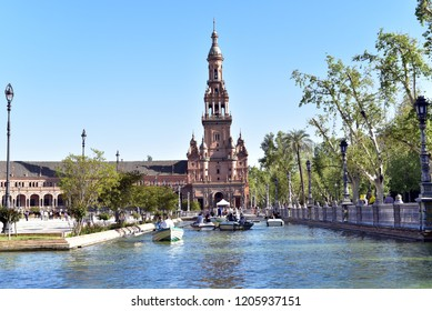 SEVILLE - SPAIN / 04.07.2017: Tourists rowing boats at the canal with north tower at the bottom