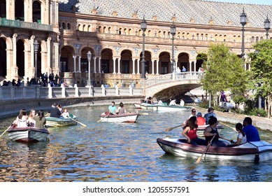 SEVILLE - SPAIN / 04.07.207: Seville Plaza de Espana, view of tourists rowing boats on the boating lake in the Plaza de Espana on a summer afternoon, Sevilla, Andalucia, Spain