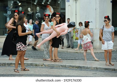 Seville, Spain - 06 21 2014: amused women in the street celebrate maiden parties and carry an inflatable man figure