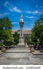 Seville, Spain : 18 June 2017: The monument to the Immaculate Conception in the Plaza del Triunfo. It has Virgin of Immaculate Conception on the top. The statues of Juan de Pineda, Bartolome Esteban