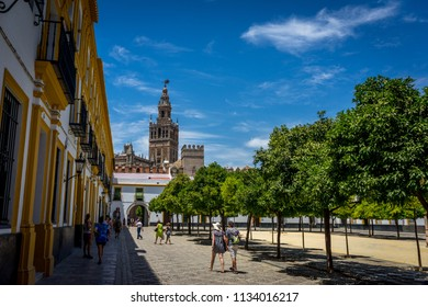Seville, Spain : 18 June 2017: The Giralda Bell tower with people in the foreground. The Giralda Tower Is The Symbol Of Seville.