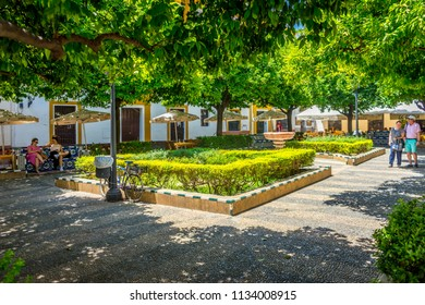 Seville, Spain - 18 June 2017:Toursist visit the famous square in Seville where you have blue beches to sit and water fountain with trees for shade, Europe