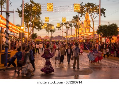 SEVILLE, SPAIN - APR, 25: people walking on the sunset street and celebrating at the Seville's April Fair on April, 25, 2014 in Seville, Spain