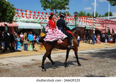 SEVILLE, SPAIN - APRIL 12, 2008 - Spanish couple in traditional dress sitting on a horse with Casitas to the rear at the Seville Fair, Seville, Andalusia, Spain, Western Europe, April 12, 2008.