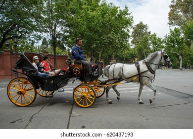 SEVILLE, SPAIN - APRIL 13, 2017: Horse drawn carriage for tourists on the streets of Sevilla, Andalusia. Beautiful architecture and trees at background.