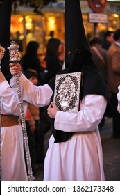 Seville, Spain - April 17, 2014: Nazarene carrying the book of rules of the brotherhood. Holy Week (Semana Santa) in Seville.
