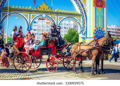 Seville, Spain - April 18, 2018: Spanish families in traditional and colorful dress travelling in a horse drawn carriages at the April Fair, Seville April Fair (Feria de Sevilla).