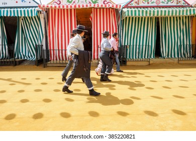 "SEVILLE, SPAIN - APRIL 23, 2015: Riders walk through the April Fair Seville dressed in tradional ""traje corto"" with casetas behind on April, 23, 2015 in Seville, Spain"