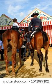 Seville, Spain - April 24, 2010: Father with his son on horseback at the April Fair, Seville Fair (Feria de Sevilla), Andalusia, Spain