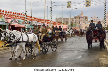 Seville, Spain - April 25, 2015: Parade of horse drawn carriages on Antonio Bienvenida street with casetas and Main Gate 2015 Seville April Fair