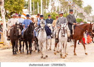 SEVILLE, SPAIN - APRIL 26, 2012: Group of men riding horses during the Seville April Fair