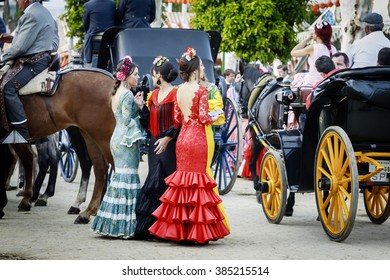 SEVILLE, SPAIN - APRIL 28, 2015: Young women wearing traditional flamenco dress at the April Fair Seville on April, 28, 2015 in Seville, Spain