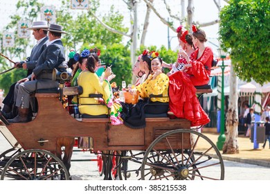 SEVILLE, SPAIN - APRIL 28, 2015: Young and beautiful women on a horse drawn carriage during the the April Fair of Seville on April, 28, 2015 in Seville, Spain