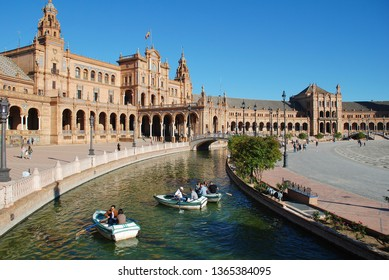 SEVILLE, SPAIN - APRIL 3, 2019: People row boats on the moat at the historic Plaza de Espana. It was built for the 1929 Ibero - American Exposition.