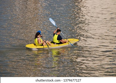 SEVILLE, SPAIN - APRIL 3, 2019: Young people paddle a kayak on the Guadalquivir river. The river is used for a variety of recreational activities.