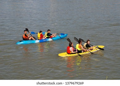 SEVILLE, SPAIN - APRIL 3, 2019: Young people paddle kayaks on the Guadalquivir river. The river is used for a variety of recreational activities.