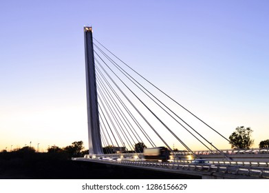 Seville, Spain - April 7, 2016: Puente del Alamillo - modern road bridge with blurred cars illuminated at dusk in Seville Spain Europe. Designed by Santiago Calatrava.