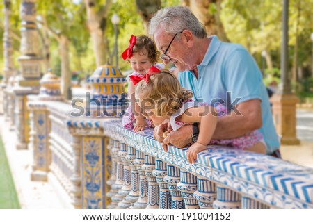 SEVILLE, SPAIN - AUG 2: Grandparents and kids play outside Plaza Espana on Aug 2, 2013 in Seville, Spain. It is a landmark example of the Renaissance Revival style in Spanish architecture.