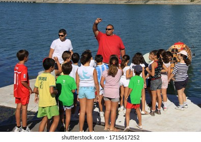 SEVILLE, SPAIN - JULY 14, 2011:Training of young rowers on the Guadalquivir River in Spain.Launching the boat on the water under the guidance of a coach