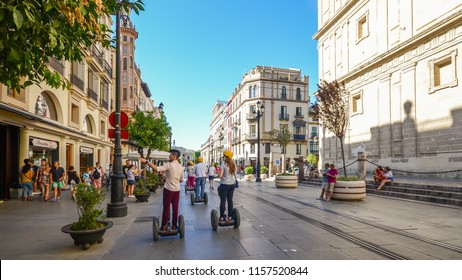 Seville, Spain - July 14th, 2018: Tourists on segways at Av. de la Constitucion in the historic centre of Seville, Andalusia, Spain