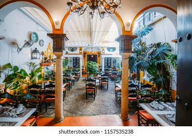 Seville, Spain - July 14th, 2018: Romantic empty Spanish restaurant courtyard in the heart of the old city of Seville
