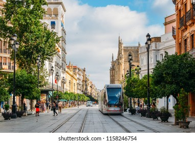 Seville, Spain - July 15, 2018: Electric tram on Constitution Avenue with iconic Seville Cathedral in background