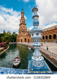 Seville Spain - July 15, 2018: Juxtaposition of blue and white ceramic azulejo tiles against one of the baroque sandstone tower at Plaza de Espana in Seville, Spain