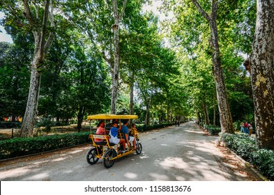 Seville, Spain - July 15, 2018: Family rides on a cycle tour bike on a path at Maria Luisa park in the summer