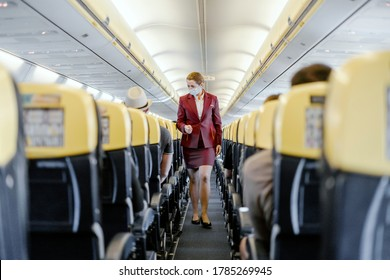 Seville, Spain - July 25, 2020: Stewardess with face mask walking in  airplane cabin among passengers