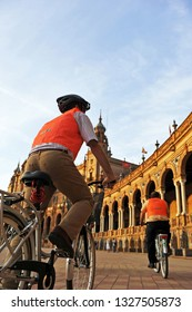 Seville, Spain - Jun 8, 2011: Cycling tourists around the Plaza de Espana (Square of Spain) designed by Anibal Gonzalez in the Maria Luisa Park for the Ibero-American Exposition of 1929.