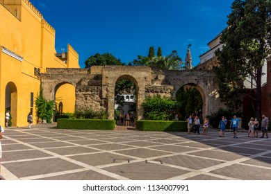Seville, Spain - June 19: the courtyard center at real Alcazar, Seville, Spain on June 19, 2017. Tourists walking in the courtyard on a warm summer day.