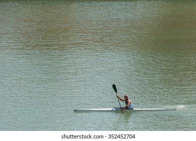Seville, Spain - June 24, 2015: Man kayaking in middle of river