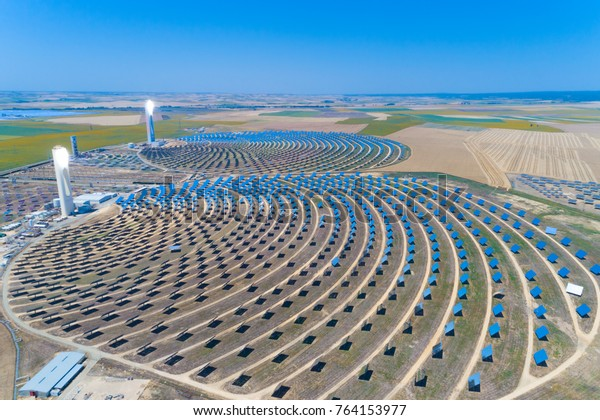 Seville, Spain - June 5 2017 : Solar tower surrounded by mirror panels harnessing the sun's rays to provide alternative renewable green energy. Situated in Andalucia, Spain.