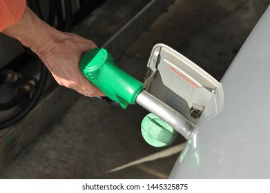 Seville, Spain - May 1, 2015: Employee of the service station filling the automobile fuel tank with gasoline seen from above