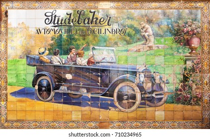 Seville, Spain - May 30 2014: Old advertising in azulejos on wall of Sevilla. Old advertising of 20's made of painted azulejos on a wall of central Sevilla. Advertising on an old car Studebaker