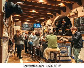 SEVILLE, SPAIN - NOV 14: Crowd of people having dinner inside tapas bar with bull head and old wine barrels on November 14, 2018. Population of Sevilla is near 750,000